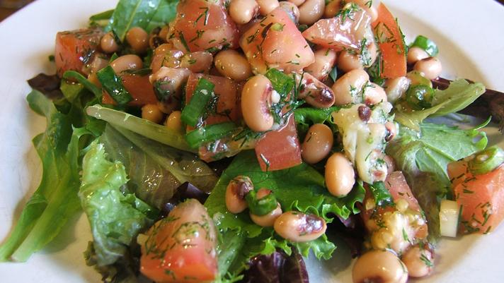 Salade de doliques et d'ail rôti sur une assiette blanche
