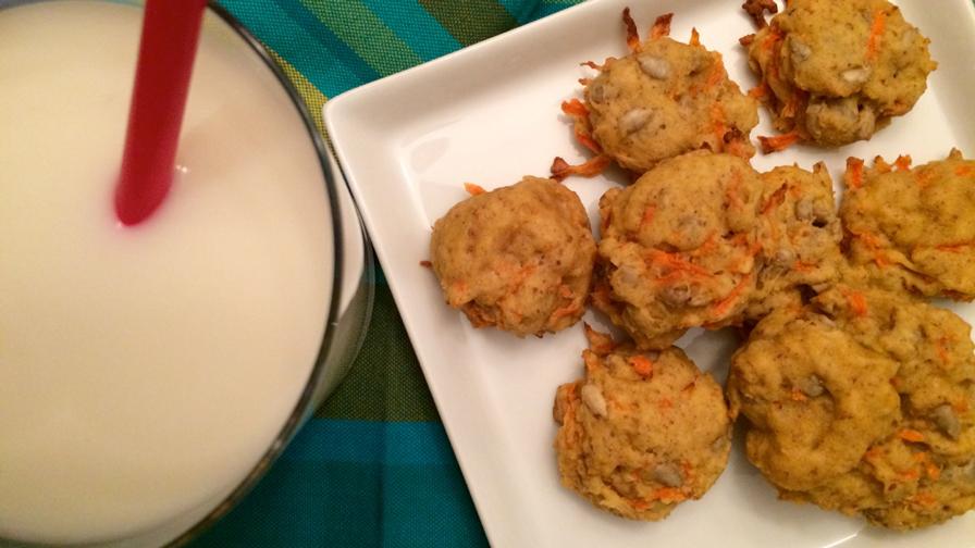 Les biscuits aux carottes sur une assiette carrée blanche.  Un verre de lait avec une paille rouge
