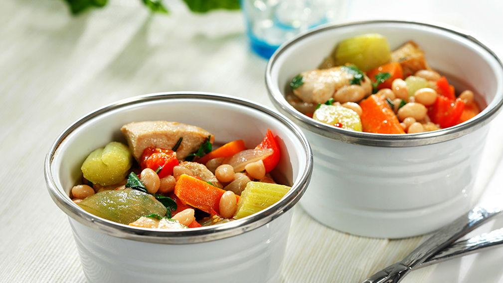 Deux bols blancs remplis de poulet cuit, de carottes, de céleri, de haricots blancs et de bouillon.