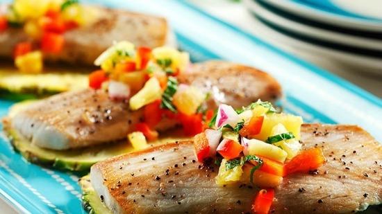 Trois morceaux de grillades mahi mahi avec salsa à l' ananas sur une plaque bleue