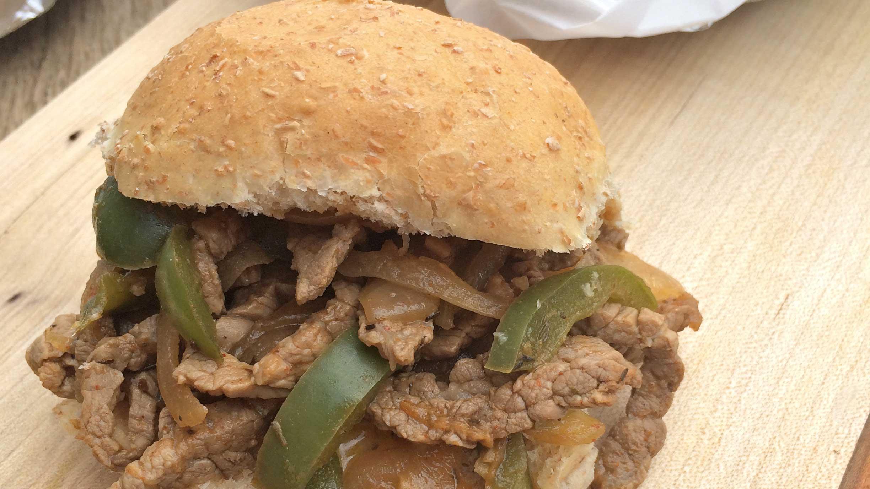 Sandwich au bifteck Philly sur feu de camp sur une planche de bois