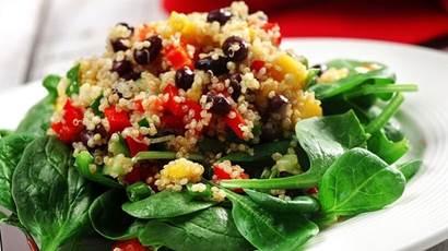 Quinoa, haché poivron rouge, mangue et haricots noirs sur lit d