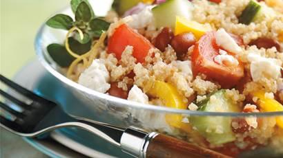 Salade de quinoa à la grecque dans un bol clair avec une fourchette