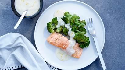 Saumon et brocoli grillés avec sauce au parmesan et au citron sur une assiette blanche avec une serviette bleue