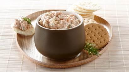 Tartinade au saumon et au yogourt dans un petit bol, servi sur un plateau en bois avec un assortiment de craquelins