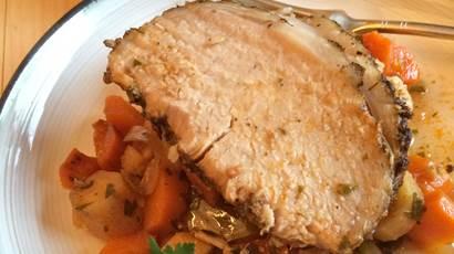 Mijoteuse rôti de porc et des légumes sur une assiette blanche avec une fourchette