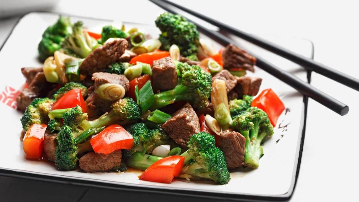 Sauté de brocoli, poivrons rouges et de bœuf sur une assiette blanche avec des baguettes