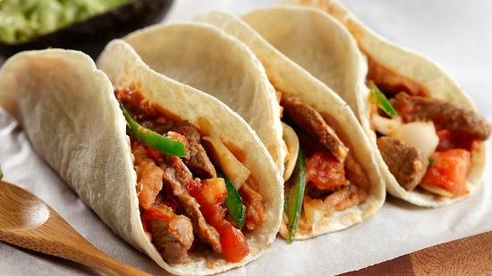 Trois tortillas remplies de steak, poivrons rouges et verts et de la salsa