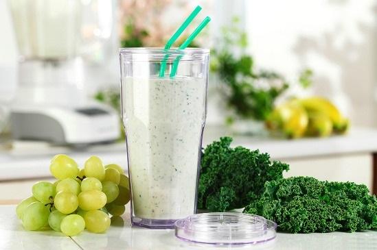 smoothie verre sur le comptoir de la cuisine avec des raisins et le chou frisé