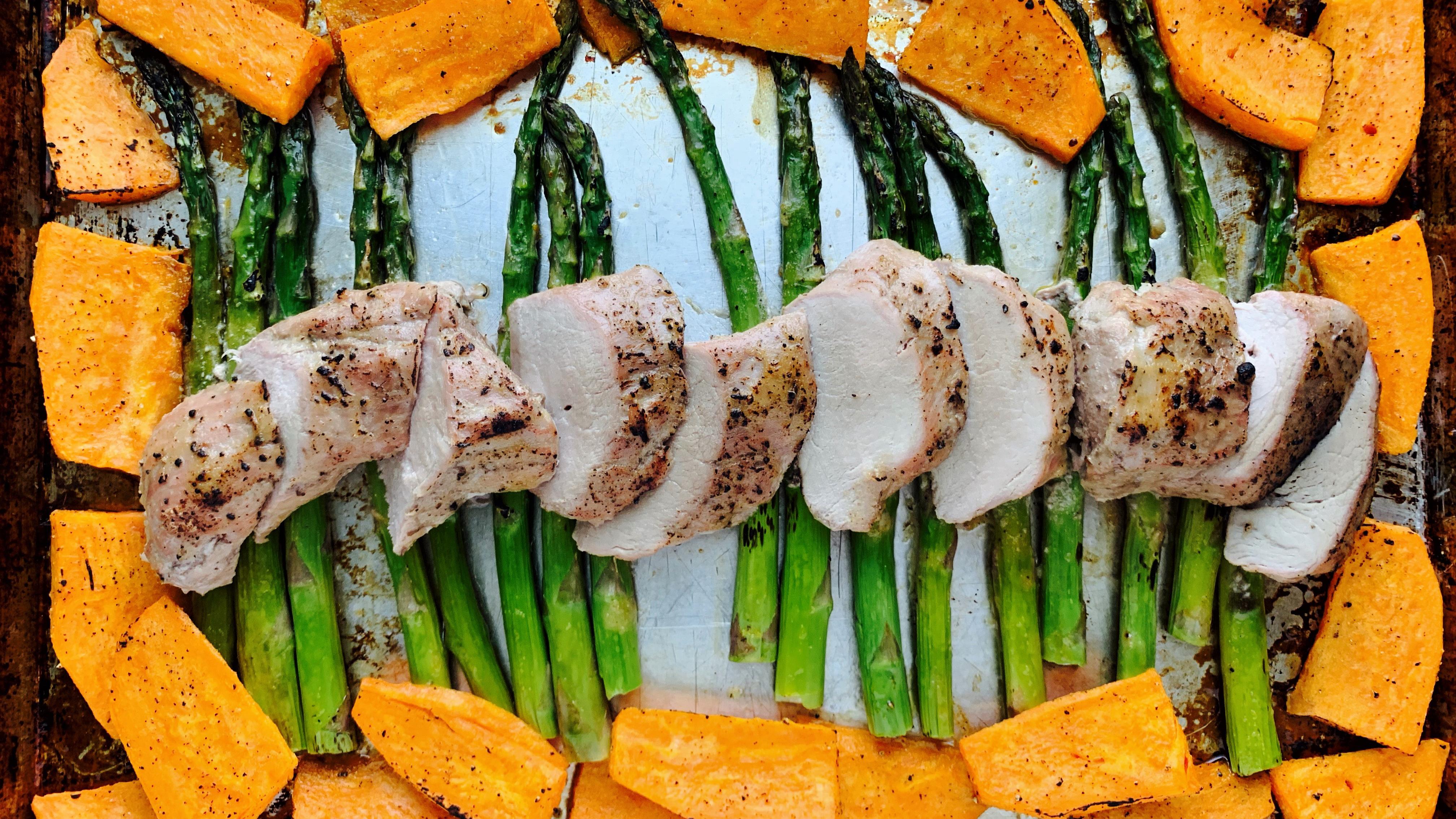 Un filet de porc sur une plaque à cuisson avec patates douces et asperges