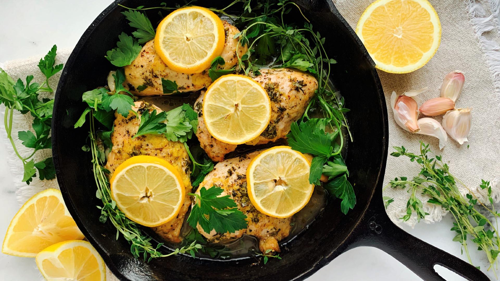 Des poitrines de poulet décorées de tranches de citron dans une poêle