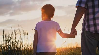 Père et fils jouant dans le parc au moment du coucher du soleil