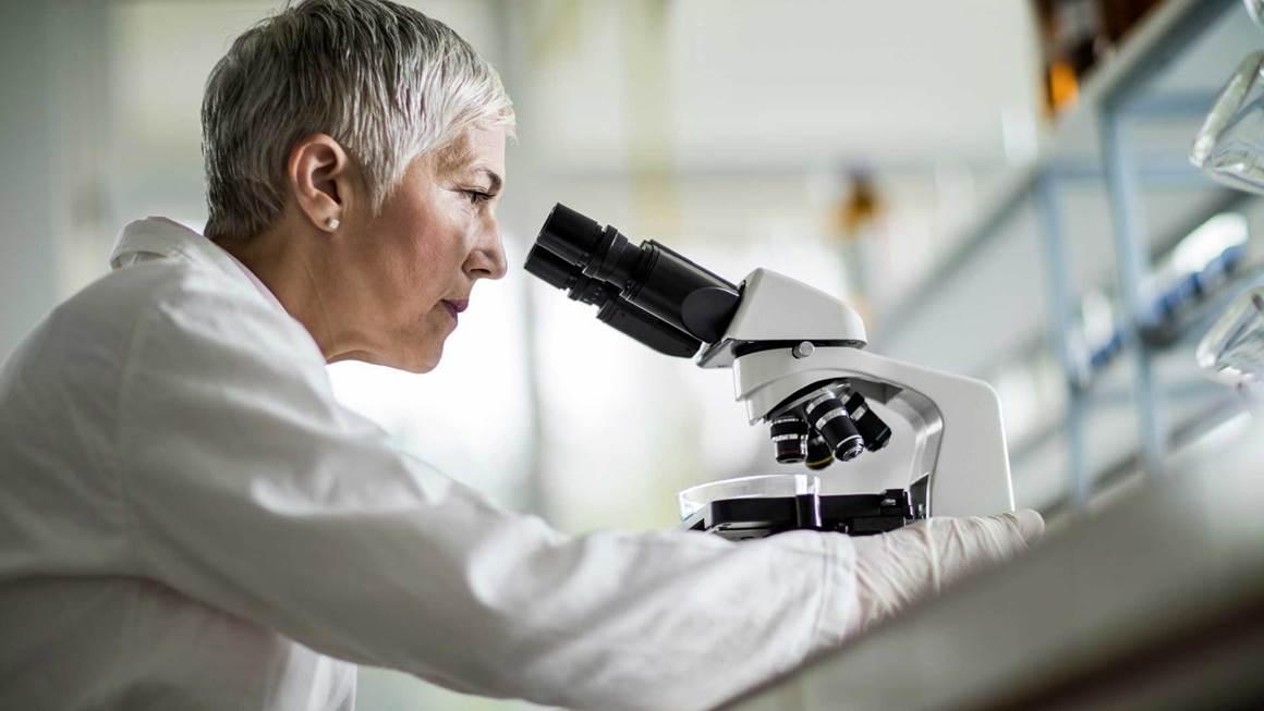 chercheur Femme utilisant un microscope à lab