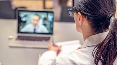 Une femme regarde un homme parler sur un ordinateur portable
