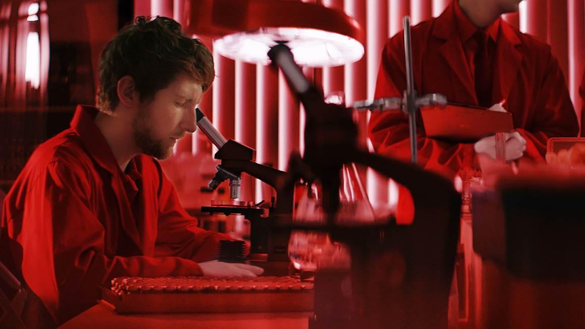 Un scientifique assis dans une pièce rouge observe quelque chose au microscope.