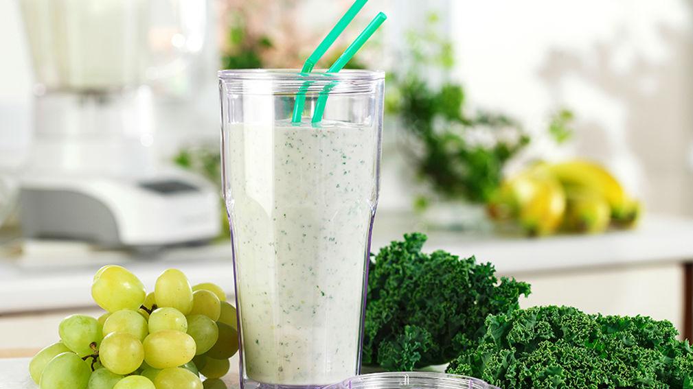 Smoothie en verre sur le comptoir de cuisine avec des raisins verts et de chou frisé.