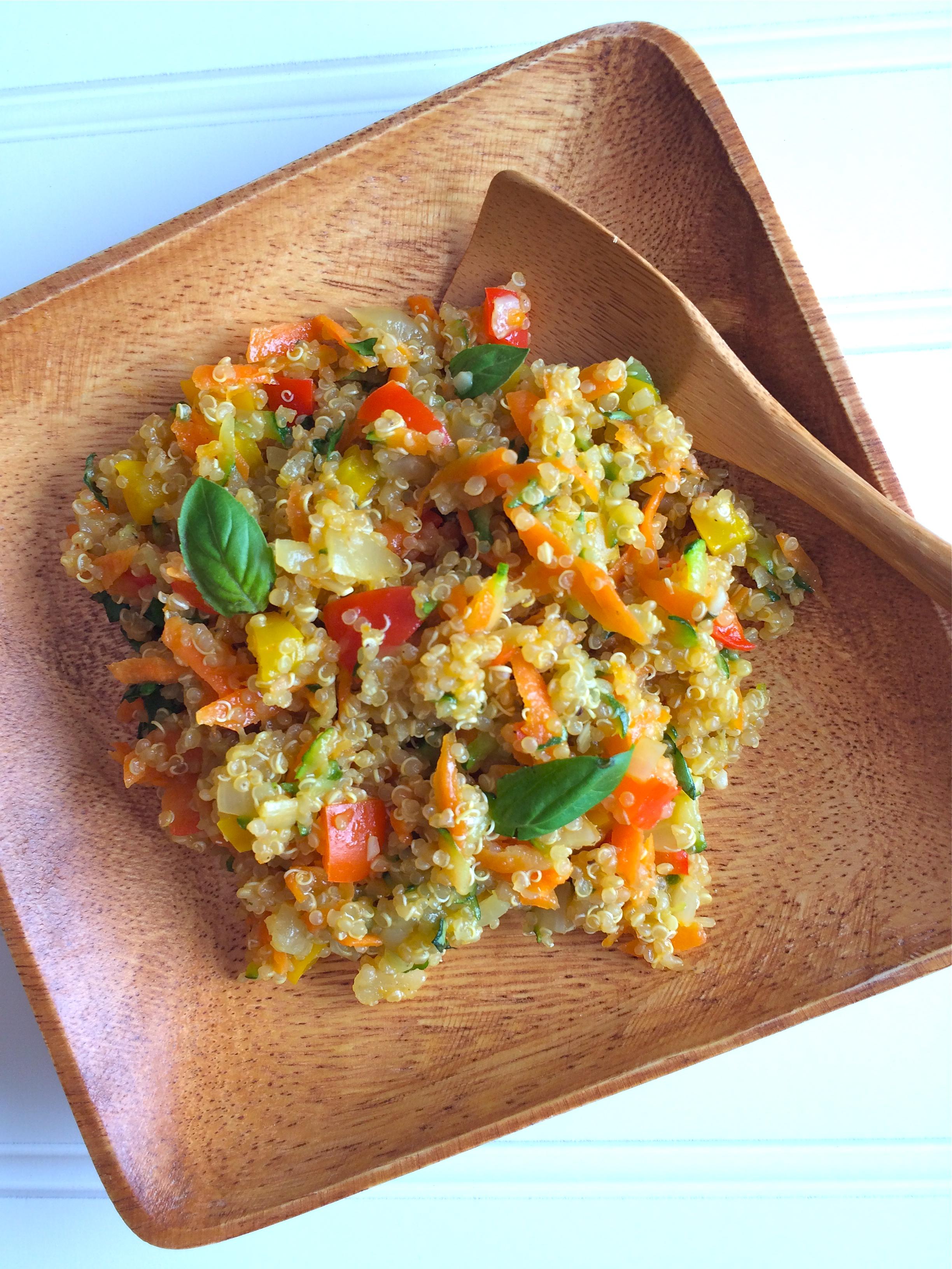 Quinoa au mélange de légumes sur une assiette en bois avec une cuillère en bois