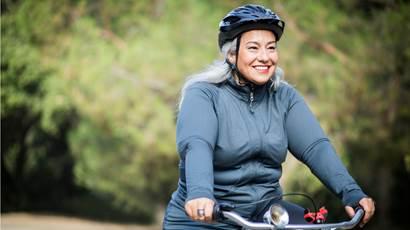 Une femme portant un casque protecteur et qui fait du vélo à l'extérieur.
